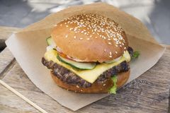 Fresh juicy tasty burger with beef on wooden table in craft pape. R Stock Photo