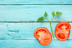 Fresh juicy tomato and green parsley on blue wooden background Royalty Free Stock Images
