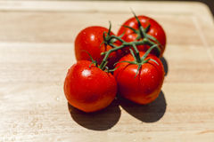 Fresh juicy tomatoes on wooden chopping board Royalty Free Stock Photos