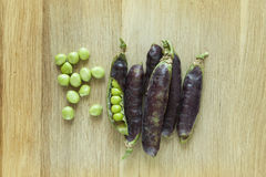 Fresh juicy violet pods and green peas Stock Image