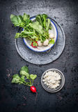 Fresh juicy white and red radishes with leaves and grain fresh cheese on dark rustic background. Top view Stock Image