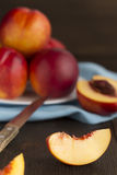Fresh juicy whole nectarines and slices on a wooden table. Royalty Free Stock Images