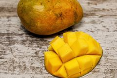 Fresh juicy yellow Thai chopped mango on the table. Fresh juicy yellow Thai chopped mango on the gray table royalty free stock images
