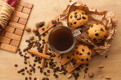 Fresh, just baked cupcakes with chocolate, cinnamon and coffee seeds set with cup of dark coffee Royalty Free Stock Image