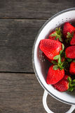 Fresh just clean wet strawberries in rustic colander Stock Image