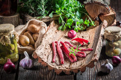 Fresh kabanos sausages on bark stock photos
