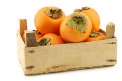 Fresh kaki fruit in a wooden crate Stock Photos