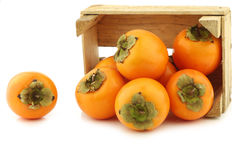 Fresh kaki fruit in a wooden crate Stock Photo