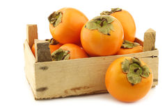 Fresh kaki fruit in a wooden crate Stock Photography