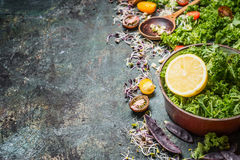 Fresh kale leaves with lemon and ingredients in old cooking pot on rustic background, Royalty Free Stock Images