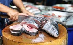 Fresh King mackerel in the market. Women chopping fresh King mackerel in the market Stock Image