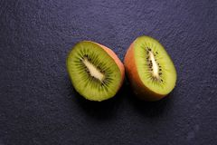 Fresh kiwi on black shale. Good quality close up photo of a chopped in a half kiwi on black shale surface, view from the top. Kiwi is one of the most popular Stock Photo