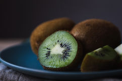 Fresh kiwi on a blue plate Stock Images