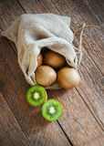 Fresh Kiwi fruit in bag on brown wooden background Royalty Free Stock Photography