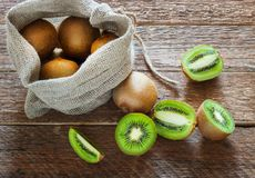 Fresh Kiwi fruit in bag on brown wooden background Stock Photography