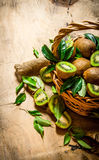 Fresh kiwi fruit in an old basket with leaves. Royalty Free Stock Photography