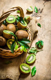 Fresh kiwi fruit in an old basket with leaves. Stock Image