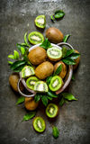 Fresh kiwi fruit in a pan with the leaves. On the stone table. Top view Stock Photos