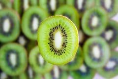 Kiwi fruit slice on kiwi background Stock Photos