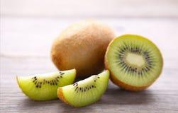Fresh kiwi fruit and slices of kiwi on grey wooden background royalty free stock images