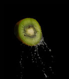Fresh kiwi fruit splashing in the water isolated. With bubbles royalty free stock photos