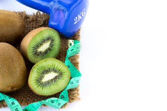 Fresh kiwi and measuring tape with blue dumbbell on sackcloth Stock Image