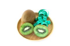 Fresh kiwi and measuring tape in wooden pate Royalty Free Stock Photography