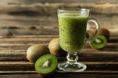 Fresh kiwi smoothie in glass on brown wooden baclground. Fresh kiwi smoothie in glass on brown wooden baclground Stock Images