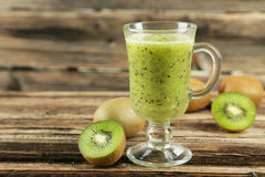 Fresh kiwi smoothie in glass on a brown wooden baclground Stock Photos
