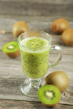 Fresh kiwi smoothie in glass on grey wooden baclground. Royalty Free Stock Photos
