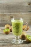 Fresh kiwi smoothie in glass on grey wooden baclground. Fresh kiwi smoothie in glass on grey wooden baclground Stock Image