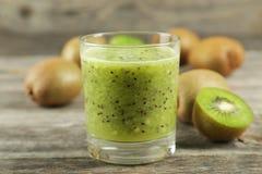 Fresh kiwi smoothie in glass on grey wooden baclground. Fresh kiwi smoothie in glass on grey wooden baclground Stock Photo
