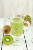 Fresh kiwi smoothie in glass on a white wooden baclground Royalty Free Stock Image