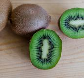 Fresh kiwi on wooden background. Fresh kiwi cut in half on wooden background detailed shot Royalty Free Stock Photography