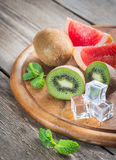 Fresh kiwifruits and grapefruit. On the wooden board Royalty Free Stock Photography