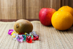 Fresh kiwis and apple with oranges. On mat ground stock photography