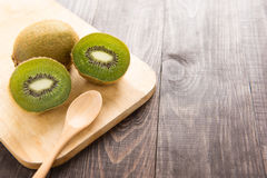 Fresh kiwis fruit and spoon on wooden board.  stock images