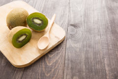 Fresh kiwis fruit and spoon on wooden board.  stock image