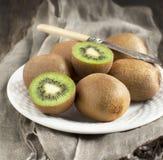 Fresh kiwis. With knife on plate stock photos