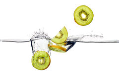Fresh Kiwis Splash in Water Isolated on White Background. Closeup of fresh and health kiwis falling into clear water isolated on white background royalty free stock images