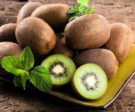 Fresh kiwis on wooden background in green plate. royalty free stock photo