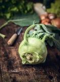 Fresh kohlrabi from garden on rustic wooden table , kitchen scene Stock Photos