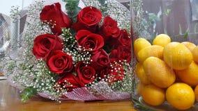 Fresh Kumquat orange in glass bottle and red rose bouquet on wooden floor. Fresh Kumquat orange in glass bottle and red rose bouquet stock image