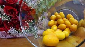 Fresh Kumquat orange in glass bottle and red rose bouquet on wooden floor Stock Images