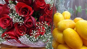Fresh Kumquat orange in glass bottle and red rose bouquet on wooden floor Royalty Free Stock Image