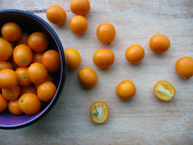 Kumquats on Wooden Cutting Board. Fresh kumquats spilling out of a black and purple bowl onto a worn wooden cutting board Stock Photography