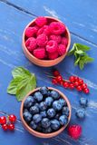 Fresh, large blueberries and raspberries in a wooden bowl close-up with mint stamens on a blue wooden background. Top view Royalty Free Stock Photography