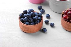 Fresh, large blueberry in a wooden bowl close-up next to other berries on a white wooden background. Top view Stock Image