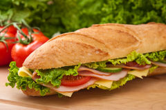 Fresh large ham & swiss sandwich. Large submarine sandwich with ham, swiss cheese, lettuce and tomatoes on a wooden cutting board Stock Photo