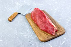 Fresh large piece of beef on a round wooden cutting board with kitchen ax. Top view on gray concrete background. Fresh large piece of pork on a round wooden Royalty Free Stock Image